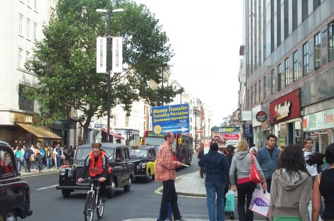 Remittance advert aimed at migrants in Oxford Street, London with Polish and Russian slogans.
