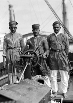Three Lascars of the ship, 'Viceroy of India', standing behind the wheel of one of the ship's tenders