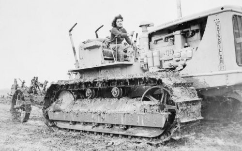 A former court dressmaker, now with the Women's Land Army, at the controls of a diesel caterpillar excavator, on a farm in Hertfordshire during the WWII.