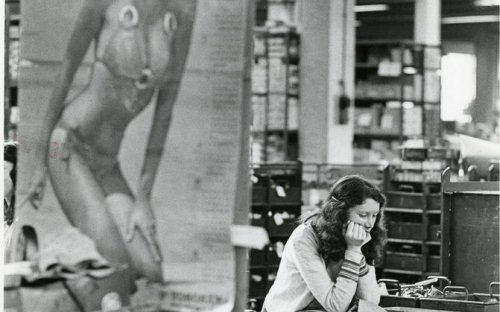 Woman factory worker in 1982, with a poster of a scantily clad woman in the foreground