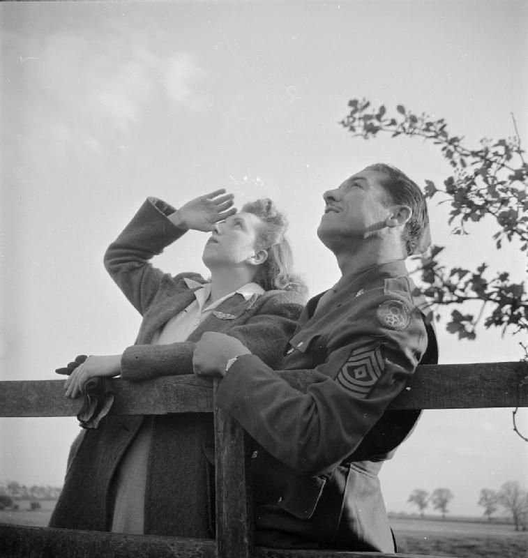 An American sergeant and his English girlfriend watch the bombers return, Chelveston, Northamptonshire.