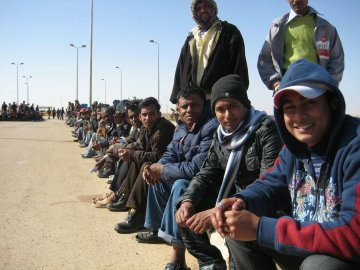 Bangladeshi migrant workers who have crossed the Egyptian border wait patiently for a repatriation flight home, relieved to have escaped the fighting in Libya.