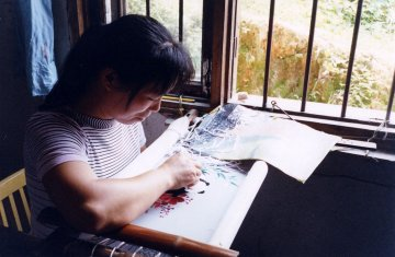 In Hunan, China, women do the famous silk-on-silk embroidery at home for factories which market it around the world.